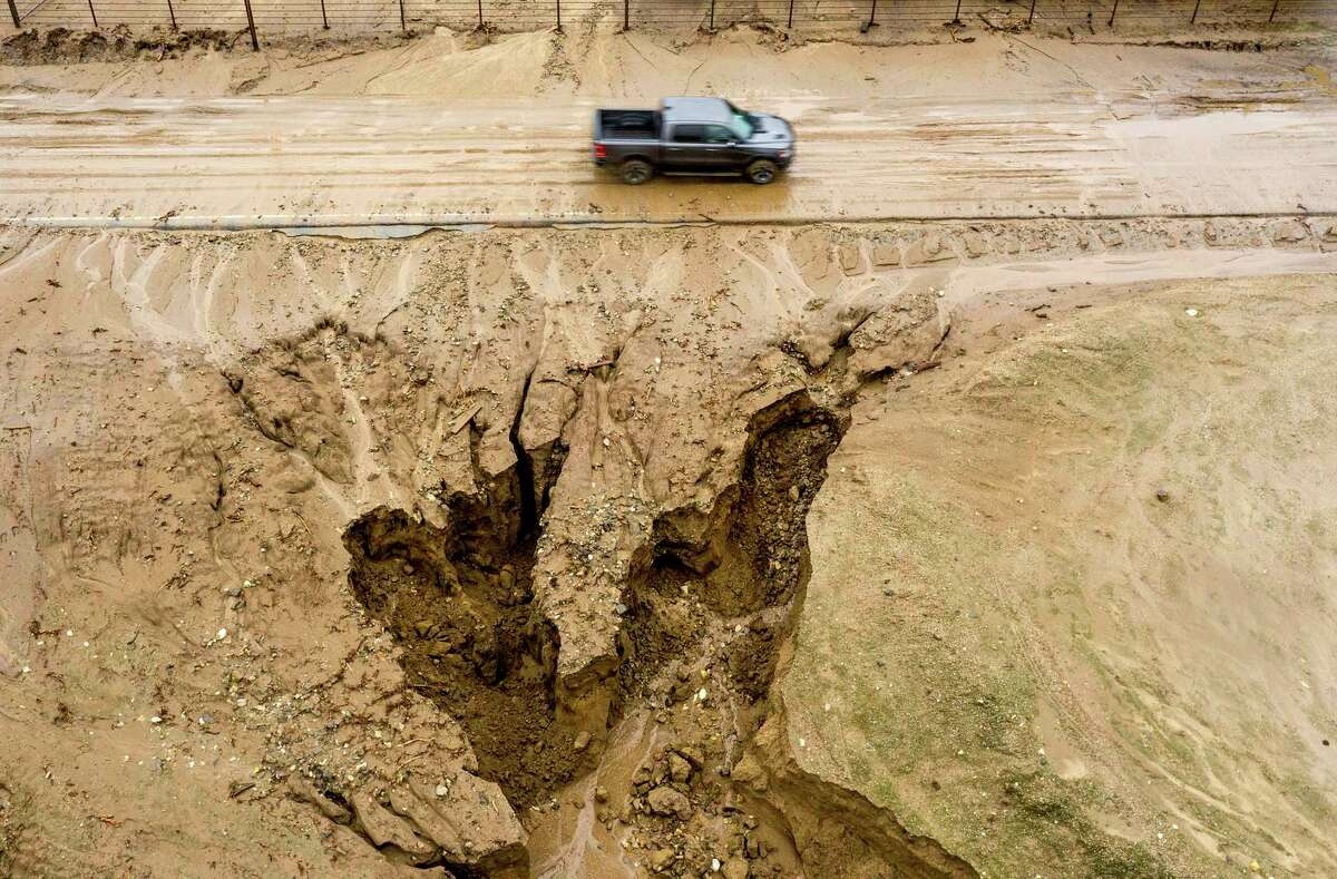 In this aerial image taken with a drone, a truck drives along River Rd. where heavy rains have caused mudslides and flooding near Salinas in Monterey County, Calif., on Thursday, Jan. 28, 2021. The area sits beneath hillsides scorched in last year's River Fire.
