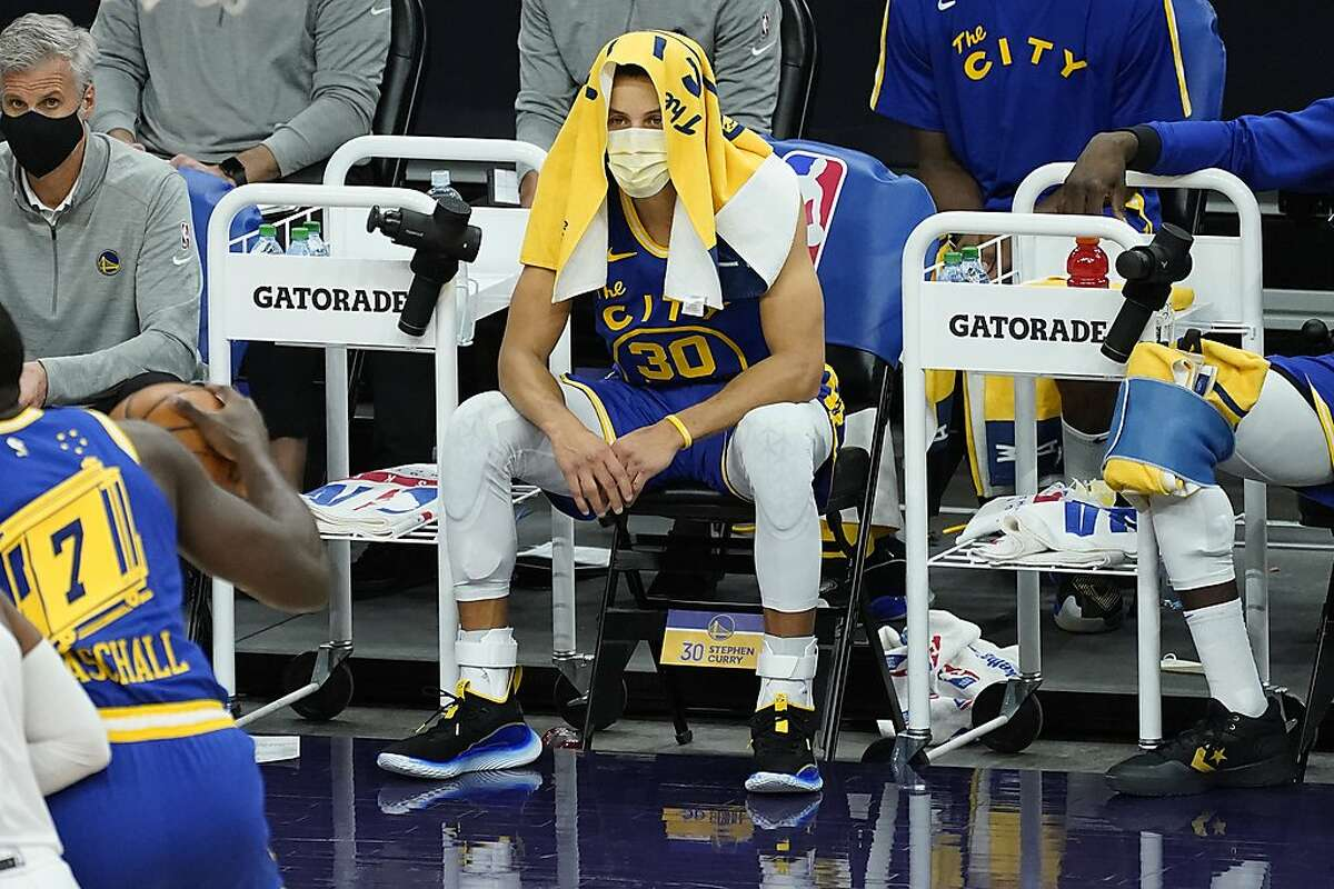 Golden State Warriors guard Stephen Curry (30) sits on the bench during the first half of an NBA basketball game against the Phoenix Suns, Thursday, Jan. 28, 2021, in Phoenix. (AP Photo/Matt York)