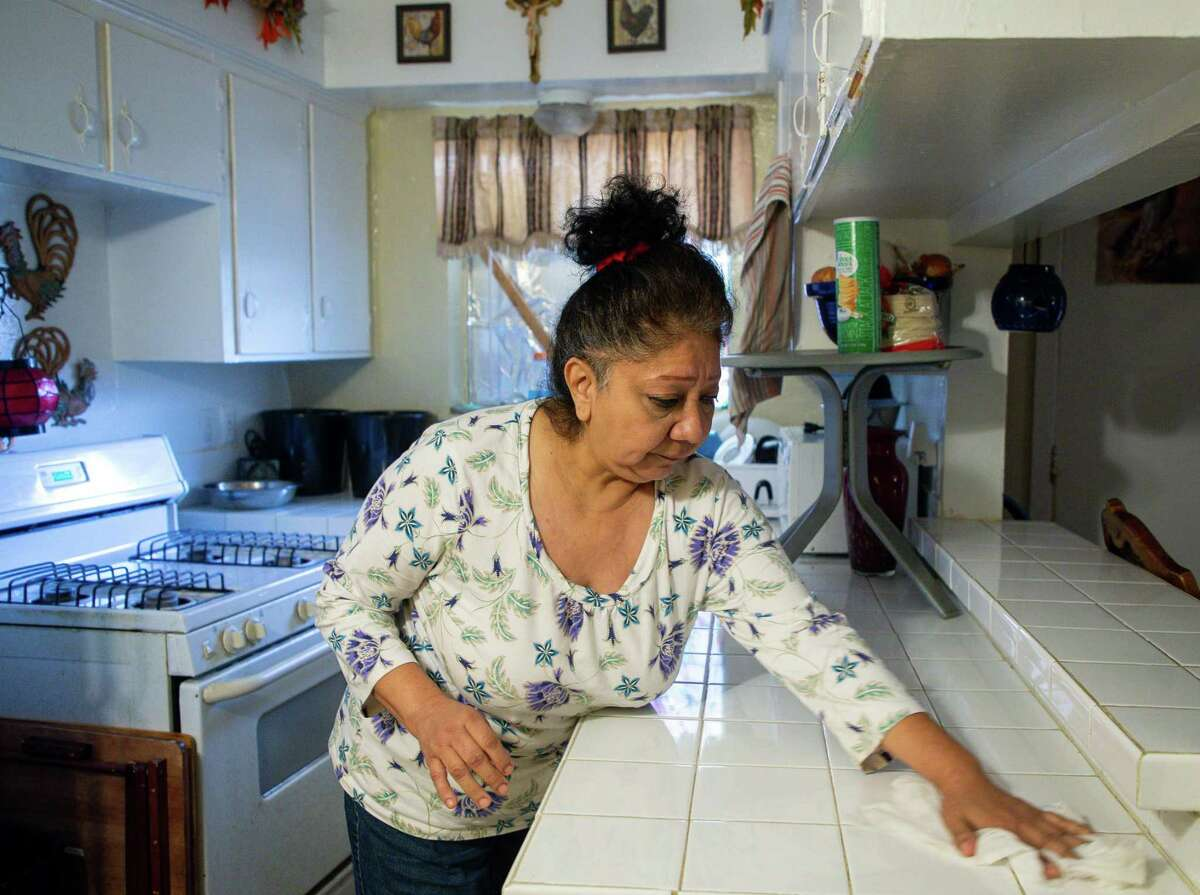Natalie Aldape, left, cleans the kitchen in her one-bedroom apartment in northwest Houston on Tuesday, Jan. 12, 2021. After a bad car accident that caused her to lose her job, Natalie became homeless, but was eventually able to get back on her feet. Then the pandemic came and she lost her job as a demolition worker and has been unemployed since the spring. She takes care of her adult son, Ernesto Lopez, who has a physical disability, and sometimes has to help him walk.