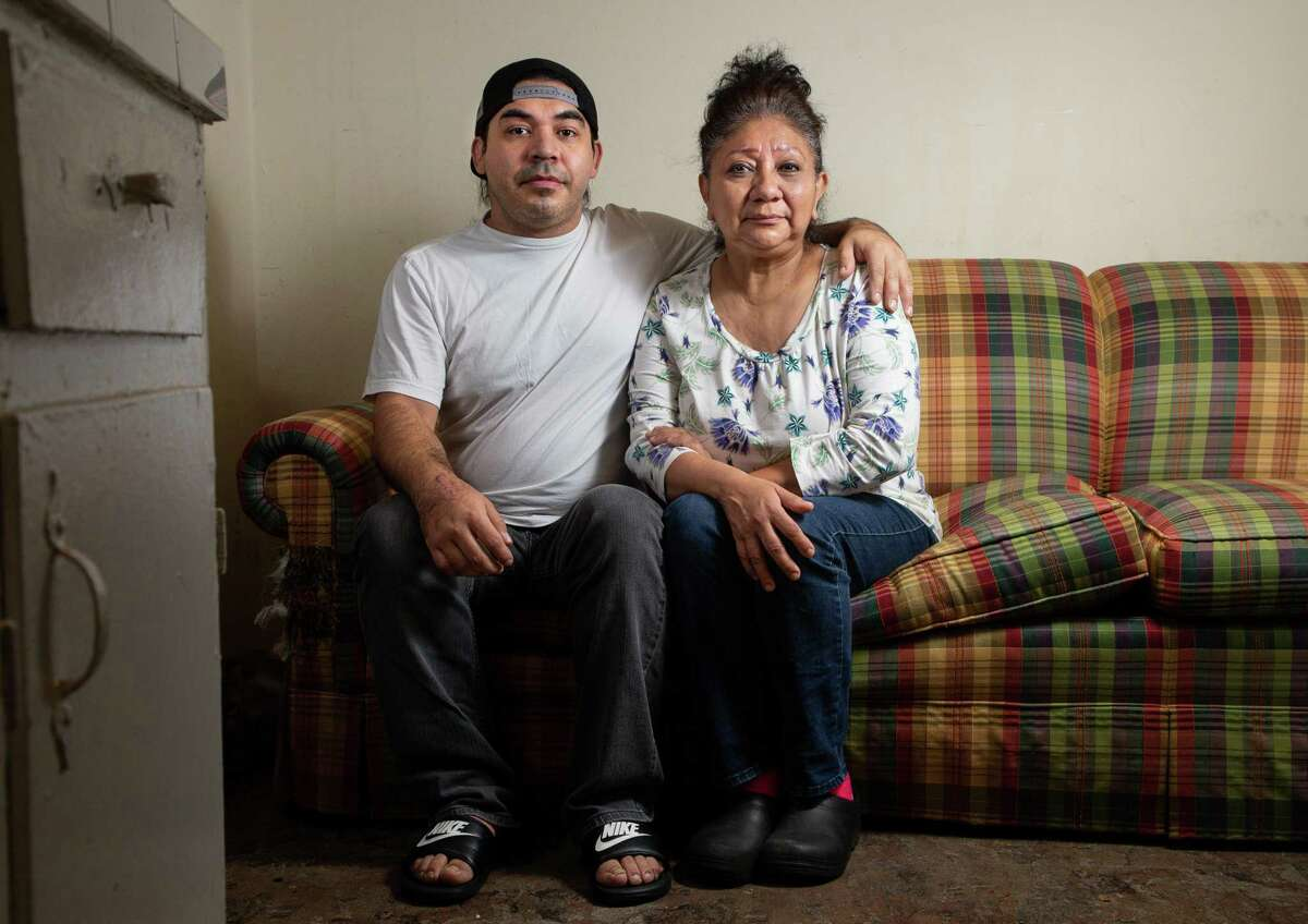 Natalie Aldape, right, and her son Ernesto Lopez pose for a photograph inside their one-bedroom apartment in northwest Houston on Tuesday, Jan. 12, 2021. After a bad car accident that caused her to lose her job, Natalie became homeless, but was eventually able to get back on her feet. Then the pandemic came and she lost her job as a demolition worker and has been unemployed since the spring. She takes care of her adult son who has a physical disability, and sometimes has to help him walk.