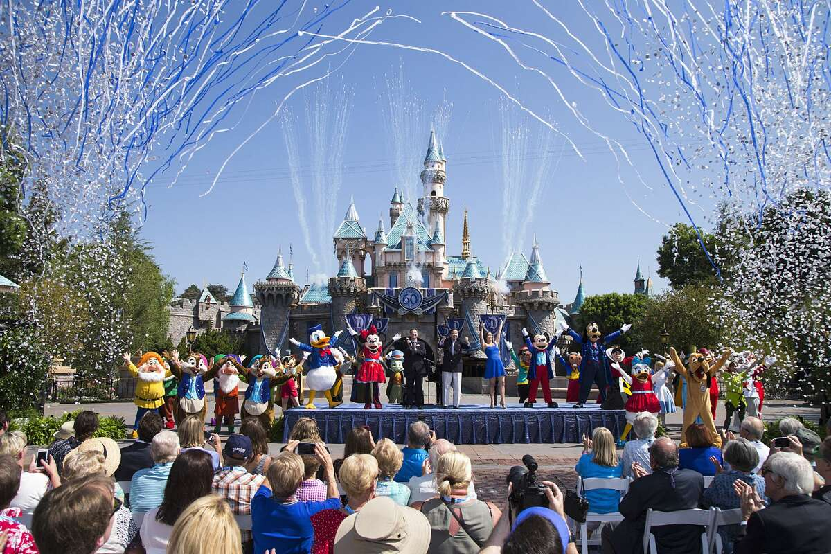 """ANAHEIM, CA - JULY 17: In this handout photo provided by Disney parks, Mickey Mouse and his friends celebrate the 60th anniversary of Disneyland park during a ceremony at Sleeping Beauty Castle featuring Academy Award-winning composer, Richard Sherman and Broadway actress and singer Ashley Brown July 17, 2015 in Anaheim, California. Celebrating six decades of magic, the Disneyland Resort Diamond Celebration features three new nighttime spectaculars that immerse guests in the worlds of Disney stories like never before with """"Paint the Night,"""" the first all-LED parade at the resort; """"Disneyland Forever,"""" a reinvention of classic fireworks that adds projections to pyrotechnics to transform the park experience; and a moving new version of """"World of Color"""" that celebrates Walt Disneys dream for Disneyland. (Photo by Paul Hiffmeyer/Disneyland Resort via Getty Images)"""