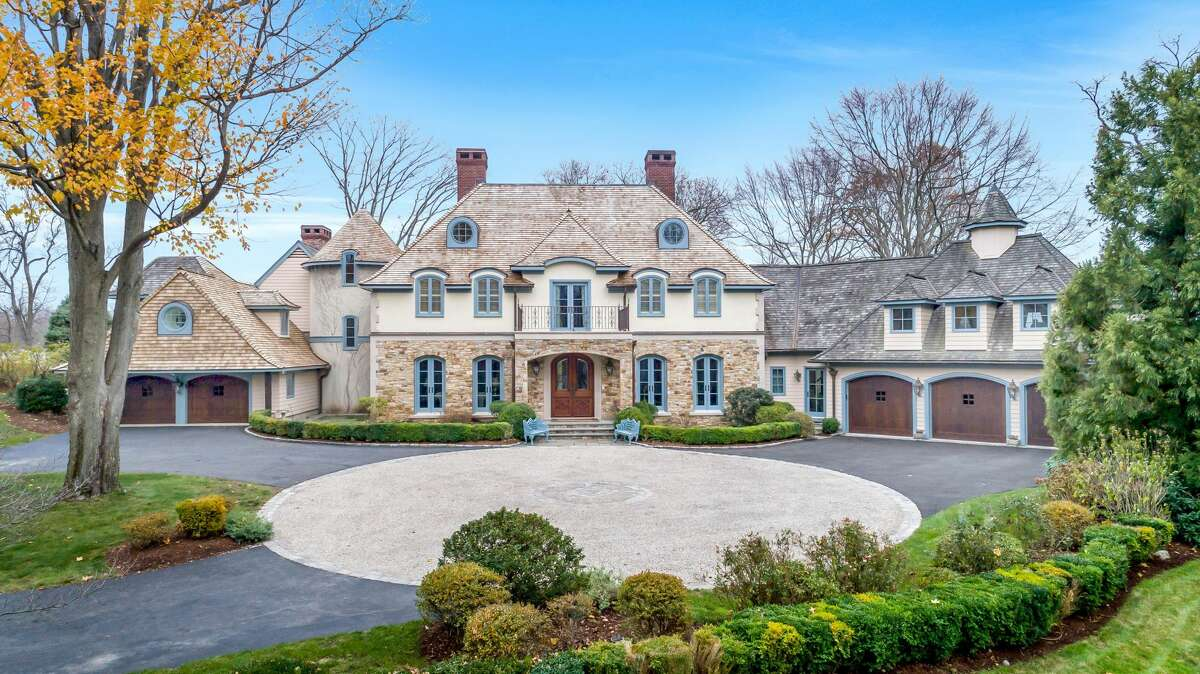 European-style stone and stucco house with a circular forecourt at 31 Swifts Lane, Darien. From its position atop a knoll looking over the pond and the iconic Ring's End Bridge, its residents enjoy views throughout the day.
