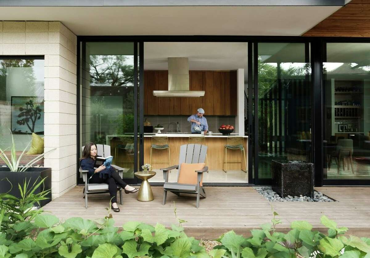 Big sliding glass doors open up the kitchen to their patio and gardens. Here, Maria Cabanillas relaxes on the patio while Kris Griffith works in the kitchen.