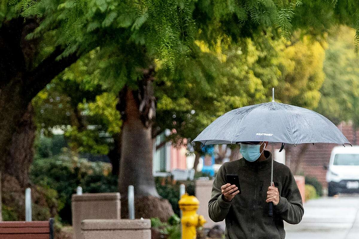 A person wears a mask while carrying an umbrella during a walk through San Jose State University's campus as rain falls in San Jose, Calif. Friday, January 22, 2021. Scattered showers are expected to soak the Bay Area Friday ahead of a series of storms predicted next week.