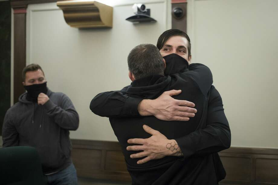 Matthew Wygant, right, hugs Greg Yancer, center, after a ceremony celebrating Wygant's graduation from the MiHope (Midland County Honest Opportunity Probation with Enforcement) program Friday, Jan. 29, 2021 at the Midland County Courthouse. (Katy Kildee/kkildee@mdn.net) Photo: (Katy Kildee/kkildee@mdn.net)