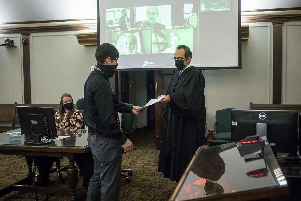 Midland County Circuit Court Judge Stephen P. Carras, right, hands a certificate to Matthew Wygant, left, celebrating Wygant's graduation from the MiHope (Midland County Honest Opportunity Probation with Enforcement) program Friday, Jan. 29, 2021 at the Midland County Courthouse. (Katy Kildee/kkildee@mdn.net)