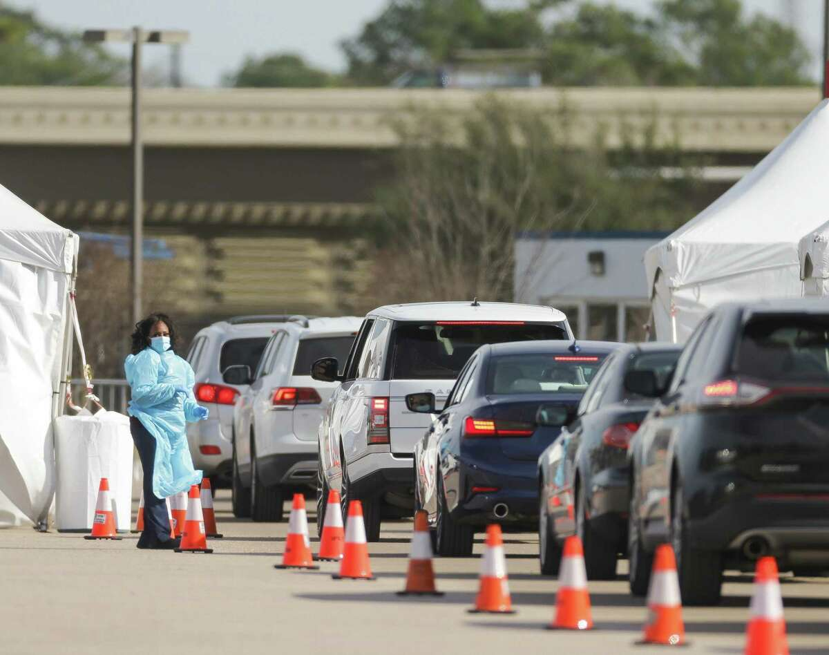Motorists make their way through the drive-thru COVID-19 vaccine line at Delmar Stadium on Jan. 27 in Houston. The city said it will not open new appointments for next week and is focusing its latest shipment on the most vulnerable.