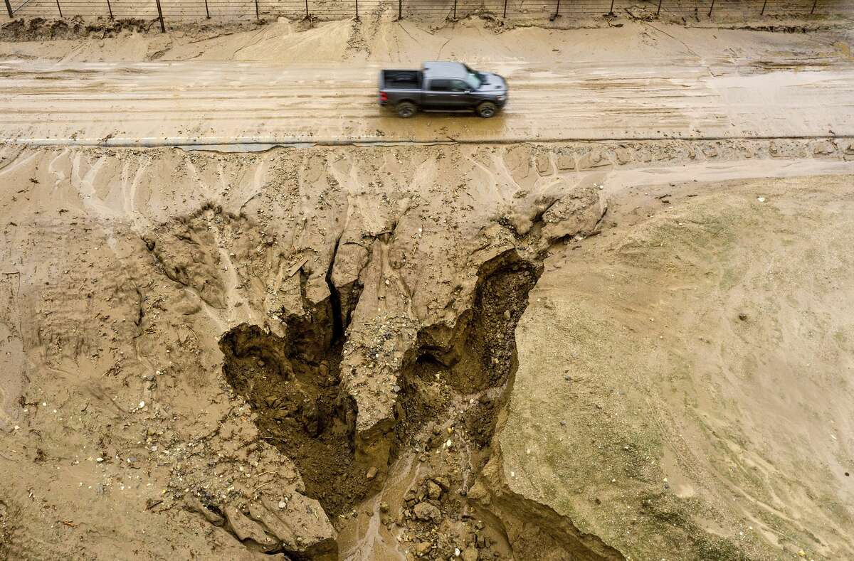 In this aerial image taken with a drone, a truck drives along River Road on Thursday, Jan. 28, 2021, where heavy rains caused mudslides and flooding near Salinas in Monterey County, Calif. The area sits beneath hillsides scorched in last year's River Fire.