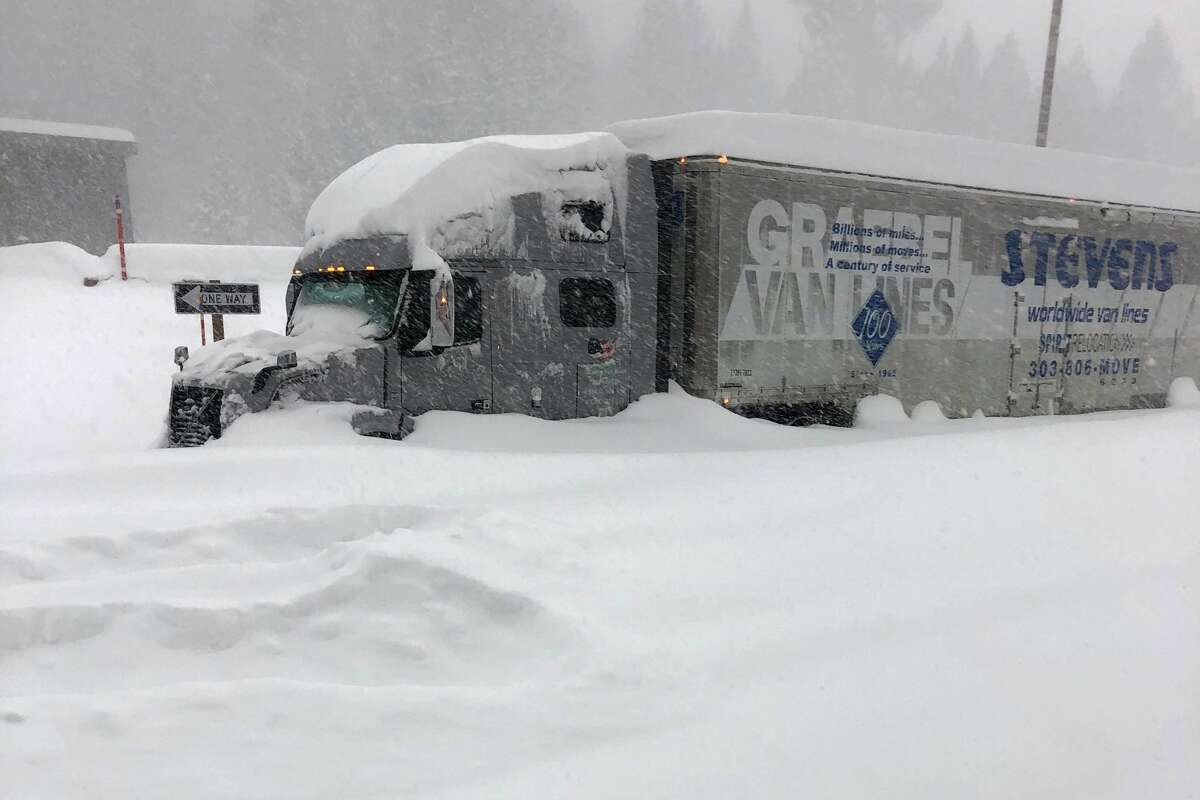In this photo provided by Caltrans District 9, a tractor trailer that is stuck in heavy snowfall at Crestview along U.S. Hwy 395, closed in Mono County, Calif., Wednesday, Jan. 27, 2021. An atmospheric river storm pumped drenching rains into the heart of California on Thursday as blizzard conditions buried the Sierra Nevada in snow.