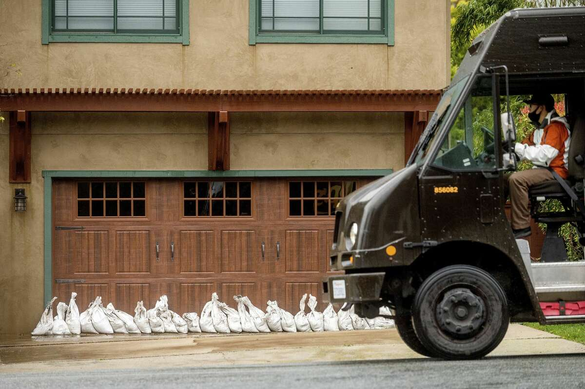 A delivery driver passes sandbags outside a Carmel, Calif. home on Thursday, Jan. 28, 2021. The area was evacuated Thursday morning as authorities feared heavy rains could send mud and water through the neighborhood. (AP Photo/Noah Berger)