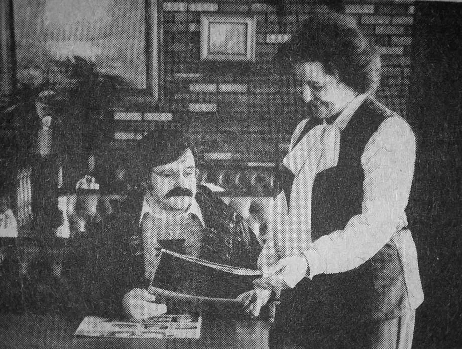 Heide Siklich, owner of Elias Brothers Big Boy, offers a menu to a customer. The above photo was published in the News Advocate on this day in 1981. (Manistee County Historical Museum photo)