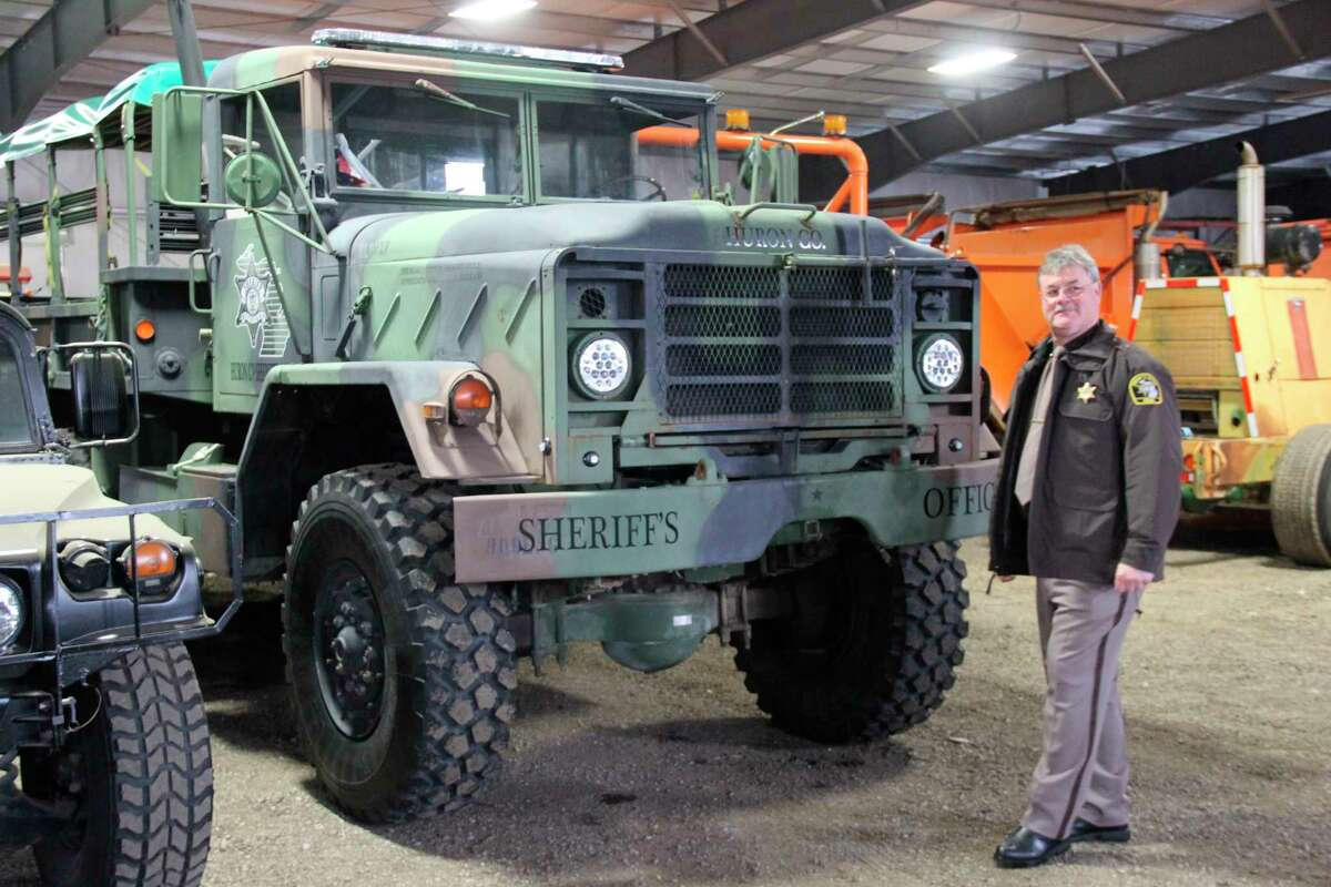 Sheriff Kelly Hanson in front of a large sheriff's department truck currently in storage. It is stored in the same garage as some sheriff's boats and humvees. (Robert Creenan/Huron Daily Tribune)