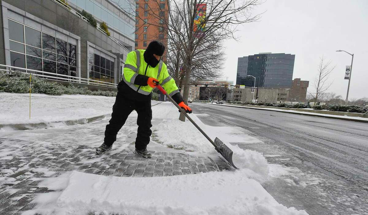 A worker clears the sidewalks in front of 1055 Washington Blvd. following a winter storm on Jan. 18, 2020 in Stamford, Connecticut that left travelers with slippery conditions and 1-2 inches of snow.