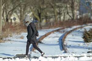 A woman walks over the old commuter train line where it crosses Main Street. There is renewed interest in the Connecticut legislature in reopening the old rail line from Danbury to Southeast, NY, to create a shortcut to Manhattan for Danbury commuters. Thursday, January 28, 2021, in Danbury, Conn.