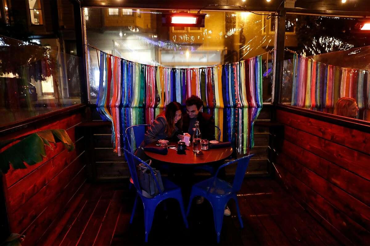 Mariah Cardenas and Yousif Damirji look at the menu at Kaiyo. Outdoor parklets like Kaiyo's stood empty for most of December and January.