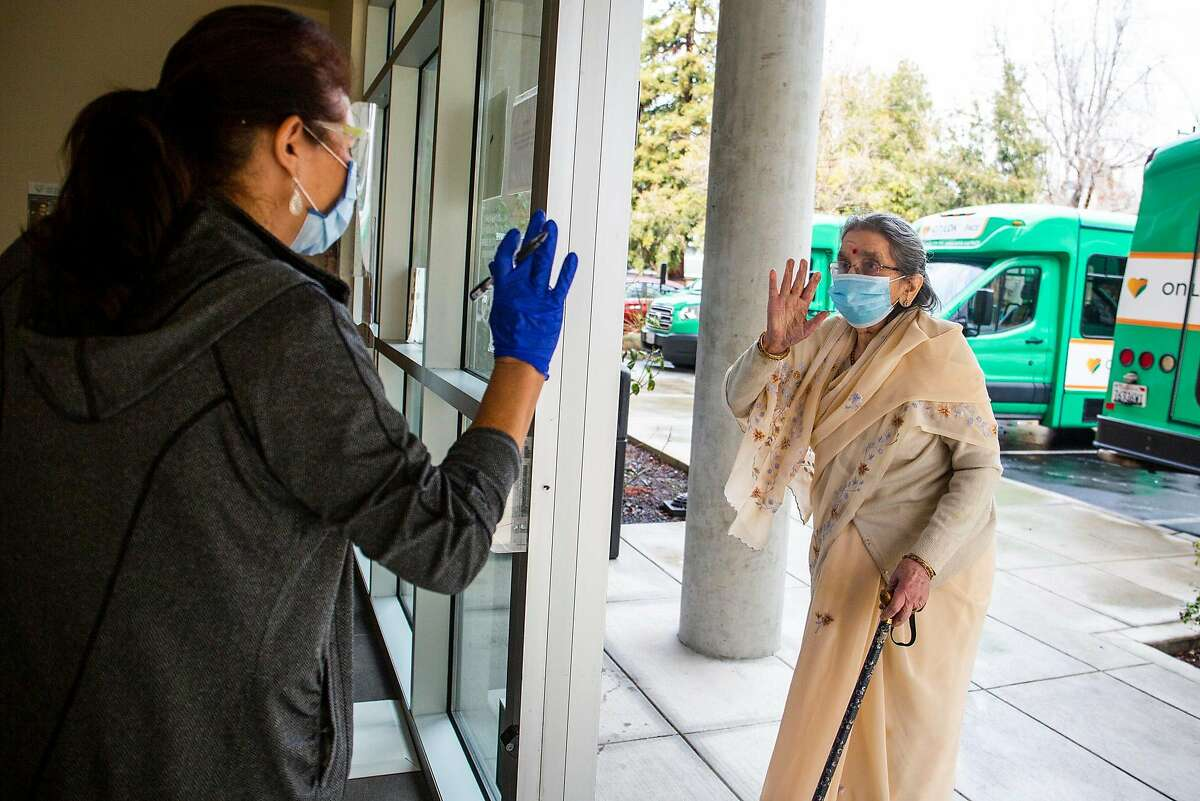 Devi Kamala, a Fremont local, waves hello to a caregiver at On Lok Pace Senior Center on her way to recieve her COVID-19 vaccine on Janurary 28, 2021.
