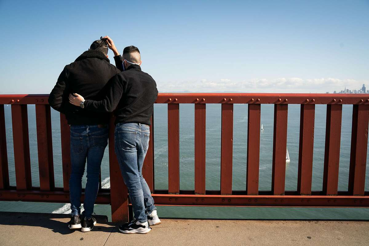 Andrew Garcia, 28, (left) and Edgar Valdivia, 30, embrace during a gathering to honor the life of their friend, Jorge Sanchez, 50, at the Golden Gate Bridge in San Francisco, Calif., on Saturday, Jan. 23, 2021.