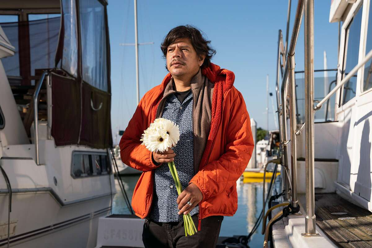 """Miguel Vazquez, 42, poses for a photo at the marina in Berkeley, Calif., on Saturday, Jan. 23, 2021. Last month, Vazquez lost his partner of 14 years, Jorge Sanchez. Vazquez believes he was an """"indirect victim"""" of the pandemic."""