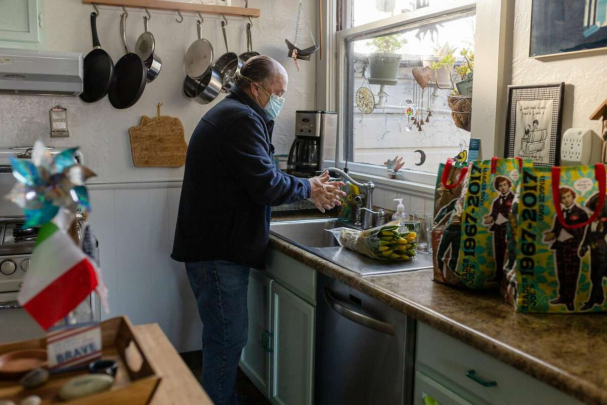 Wes Watkins washes his hands in his kitchen at his home in San Francisco's North Beach neighborhood.