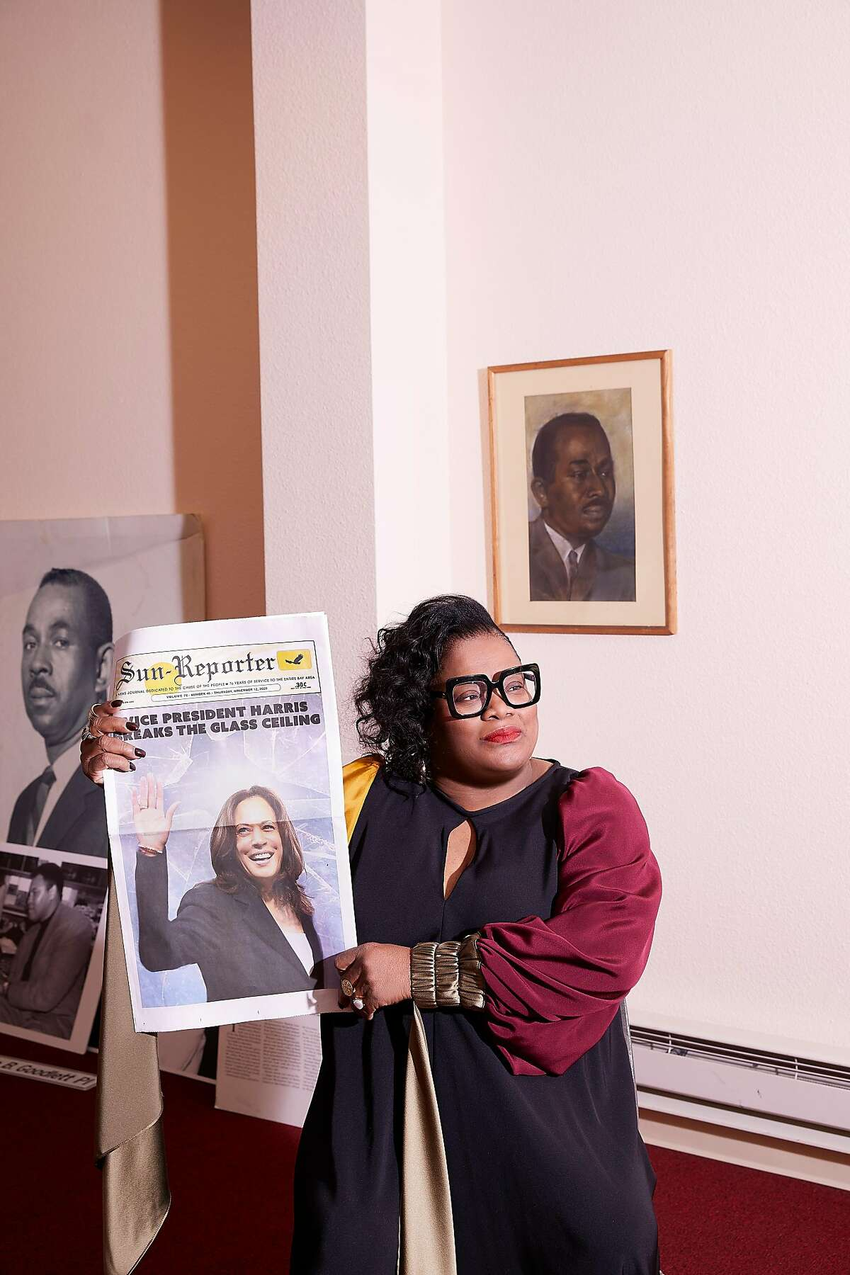 Sun-Reporter publisher Amelia Ashley-Ward poses in front of pictures of Dr. Carlton Goodlett, the iconic co-founder of the newspaper and an influential civil rights leader. She holds the Nov. 12, 2020, edition of her publication with then Vice President-elect Kamala Harris on the cover.