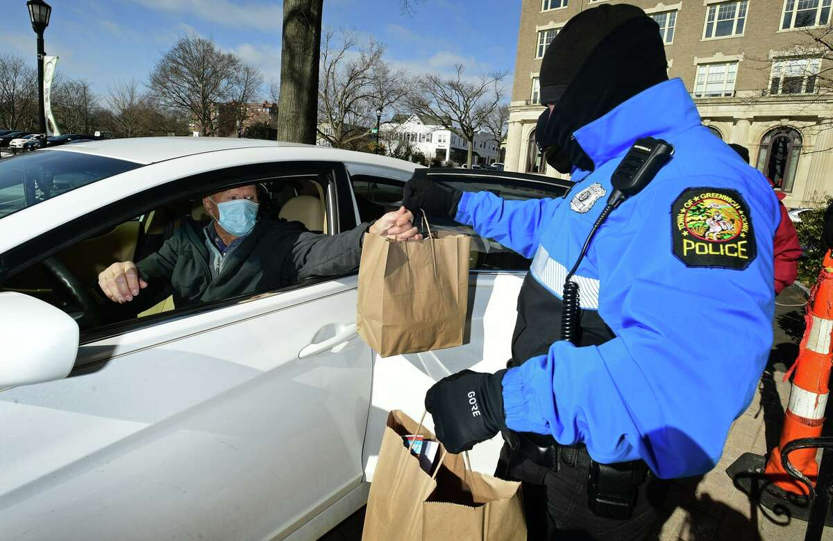 Seniors including Tom Kochan receive a drive through lunch from The Greenwich Senior Center and the Greenwich Police Bike Patrol Friday, January 29, 2021, in Greenwich. Fresh Baked Cod w/Lemon Butter Sauce was served with mashed potato, braised cabbage and chocolate chip cookies.