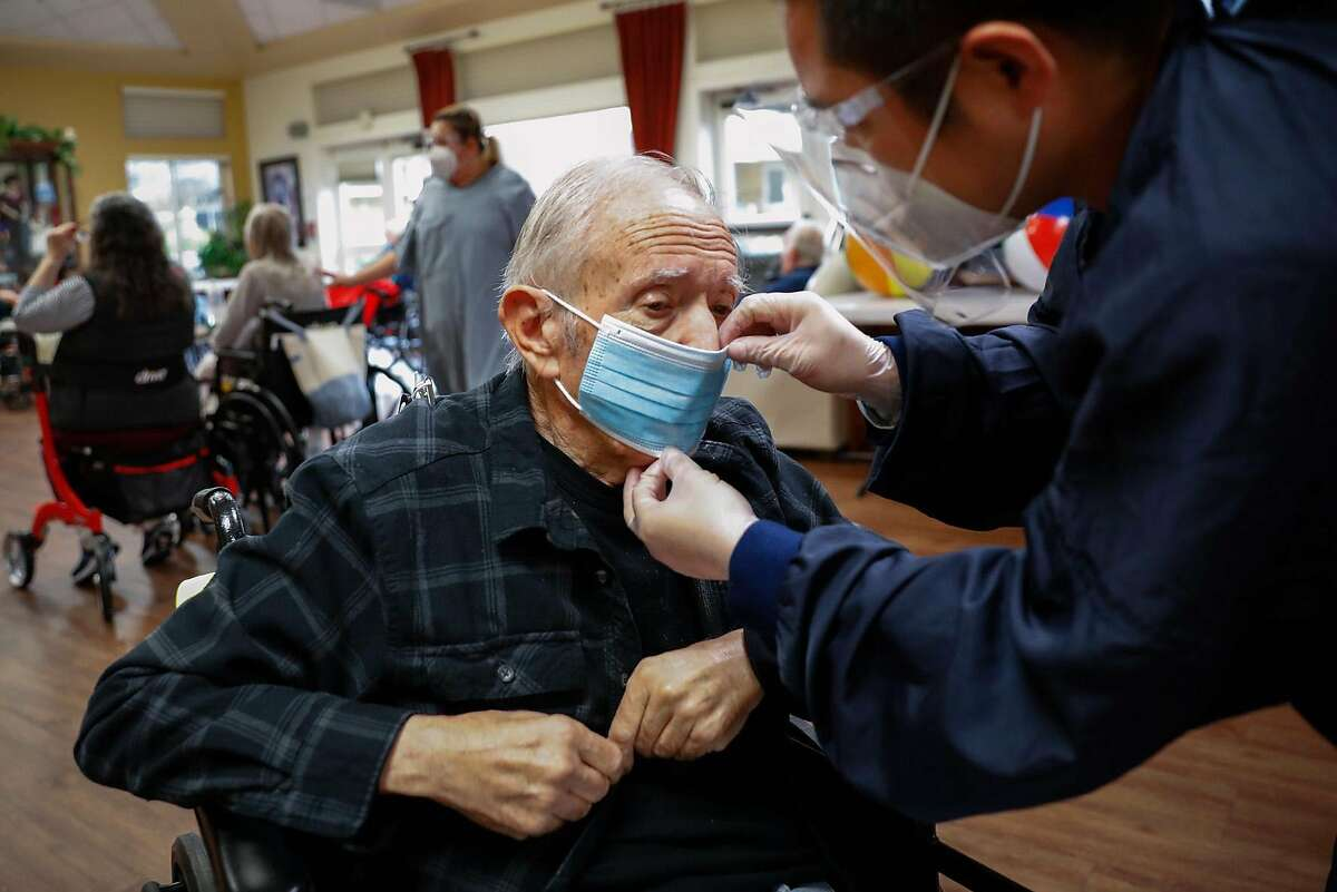 Resident Douglass Tozzini gets his mask adjusted by caregiver Joseph Salazar at Gordon Manor assisted care facility.