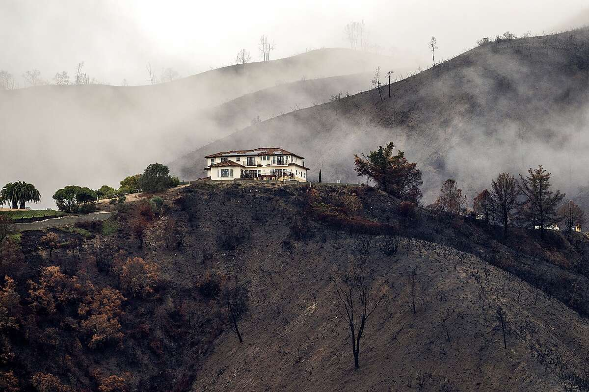 A home sits atop a hillside scorched by last year's River Fire as heavy rains caused mudslides and flooding near Salinas on Thursday.