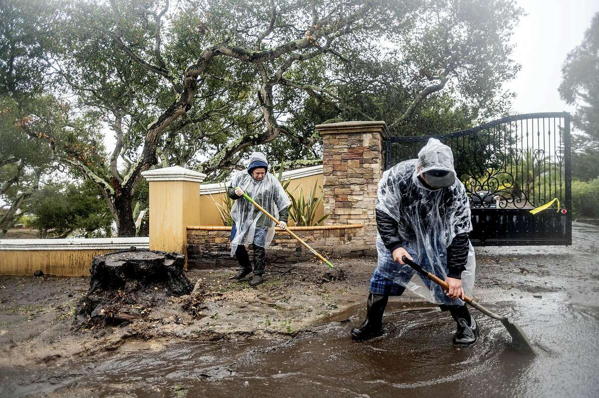 Alex (left) and Aron Moreno work to divert water from their property as heavy rains fall in Salinas, on Wednesday The couple lives below hillsides scorched in last year's River Fire where water and mud flowed downhill from burned land.