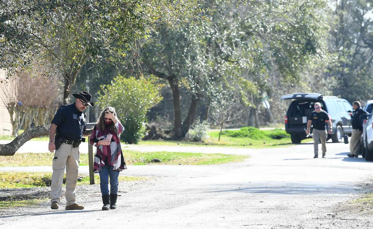 An Orange County Sheriff officer talks with a woman who rushed toward the home which was the scene of a double shooting after arriving about an hour after the incident occured Friday near Bridge City. Two people were confirmed dead by Detective Joshua Lockett. Photo taken Friday, January 29, 2021 Kim Brent/The Enterprise