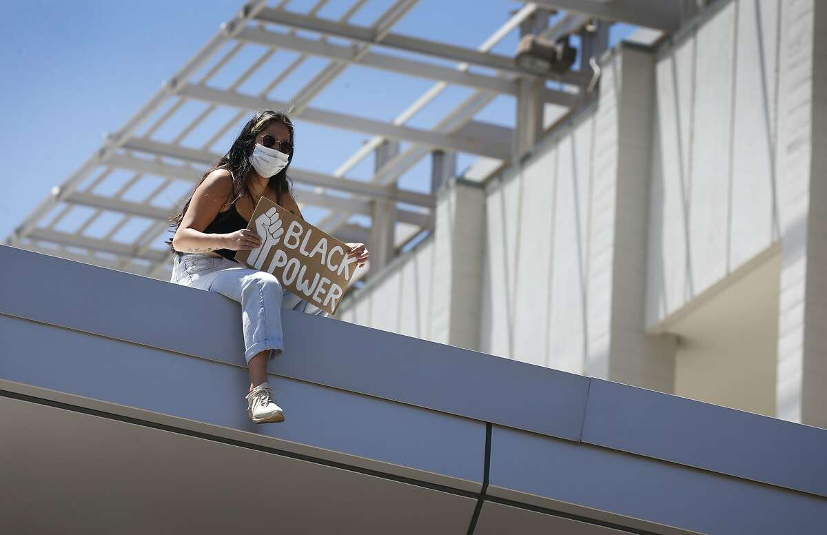 A woman sits on the roof of the student union at UC Berkeley during a racial justice demonstration in June.