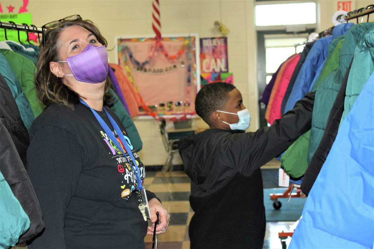 An anonymous NBA basketball player donated 300 coats to all 260 Bielefield Elementary School students through Operation Warm this week. Children were able to pick colorful outerwear they wanted from racks of coats set up in the cafeteria. Here, Principal Suzanne Shippee Lopez shares a laugh with one of the students.