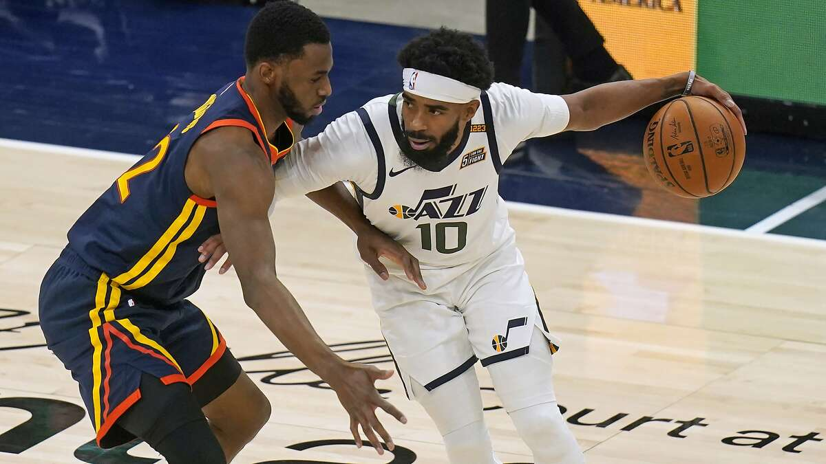 Golden State Warriors forward Andrew Wiggins, left, defends against Utah Jazz guard Mike Conley during the first half during an NBA basketball game Saturday, Jan. 23, 2021, in Salt Lake City. (AP Photo/Rick Bowmer)