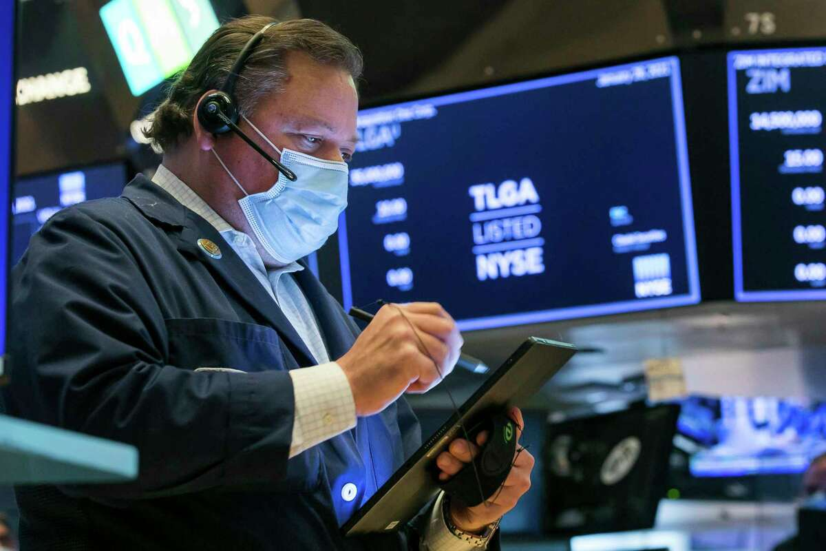 In this photo provided by the New York Stock Exchange, trader John Santiago works on the floor, Thursday, Jan 28, 2021. Amid a volatile week, Greenwich-based Interactive Brokers Group imposed new restrictions on the trading of options for companies including GameStop and AMC Entertainment.