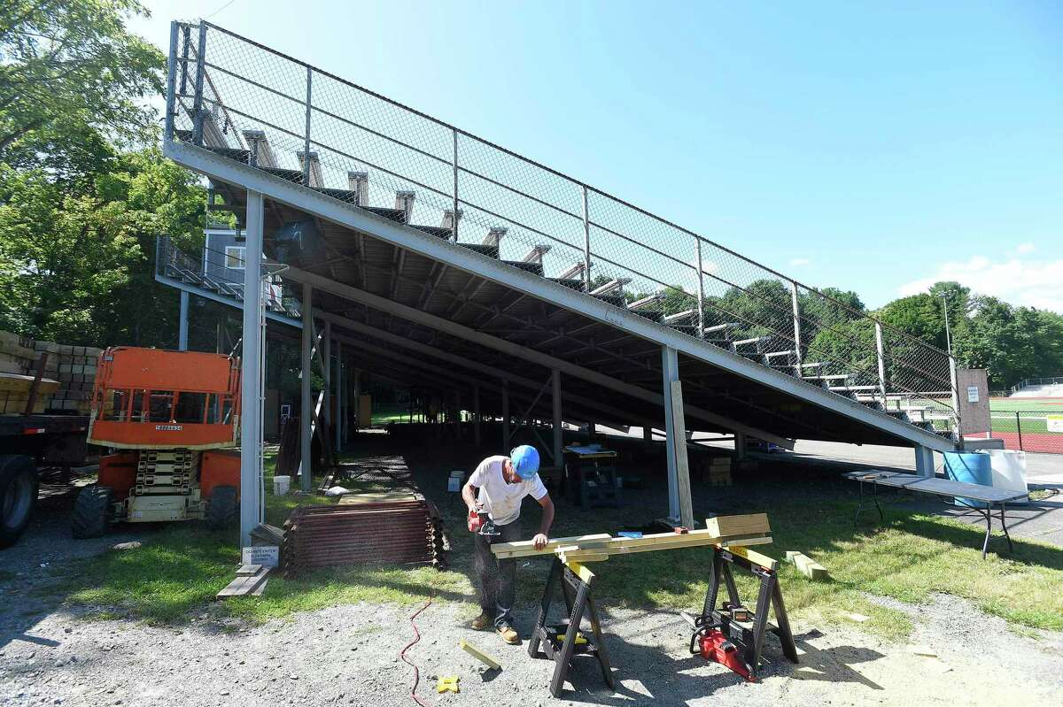 Foreman Brian Dwight, part of a crew from Veteran's Scaffold and Service Inc. out of Blackstone, Mass., cuts bracing material as they install temporary structural scaffolding support to the bleachers at Greenwich High School's Cardinal Stadium.