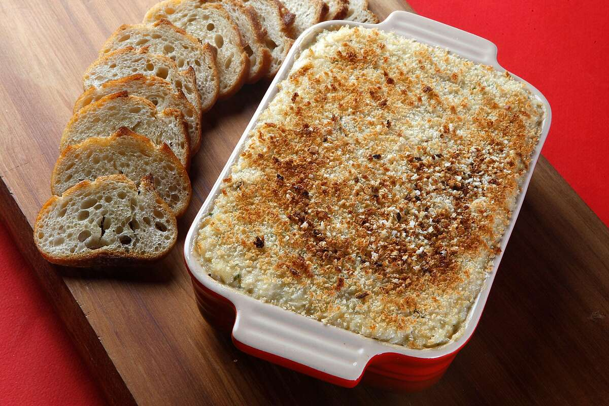 Hot crab dip with toasted baguette slices.