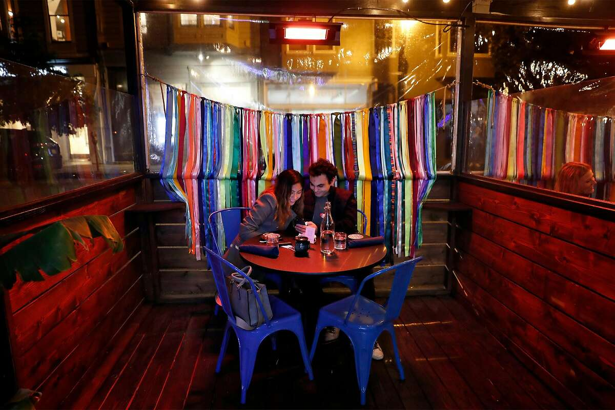 Mariah Cardenas and Yousif Damirji look at the menu as Kaiyo reopens for outdoor dining on Union Street in San Francisco.