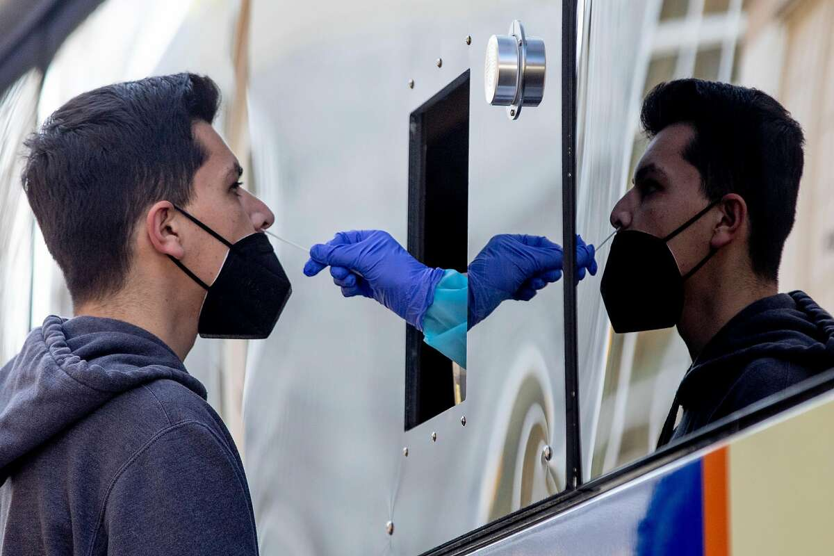 Manuel Flores gets a COVID-19 nose swab test at a BusTest Express mobile test site in Berkeley. The city offers free tests and is attempting to get more unhoused people tested for the virus.