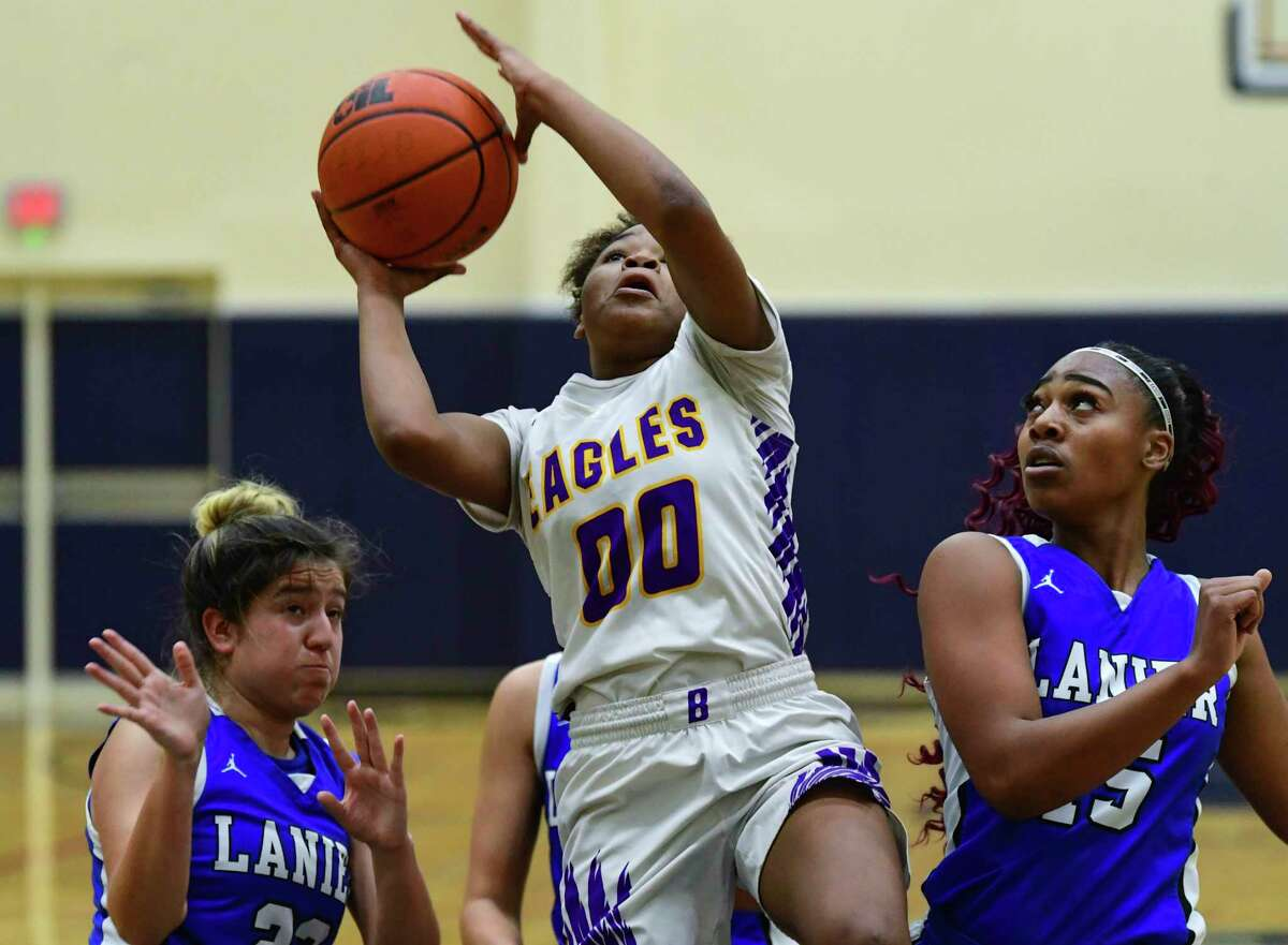 Alasia Brown (00) of Brackenridge High School penetrates and shoots as Theresa Mendiola, left, and Jakerria Mayberry, right, of Lanier High defend during high school girls basketball action in the Alamo Convocation Center on Friday, Jan. 29, 2021.