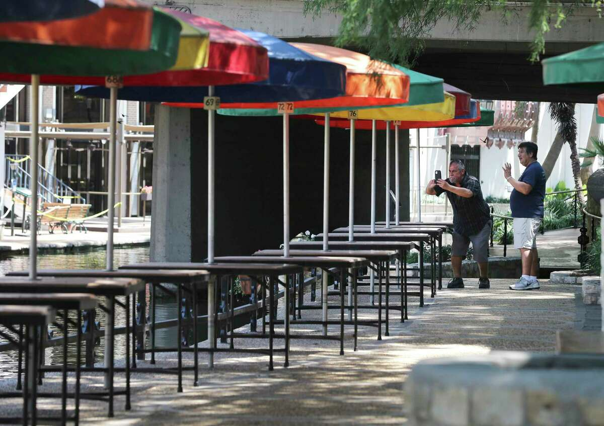 Jesse Valencia (right) and his brother, Frank, take pictures near Casa Rio Restaurant and the rows of empty tables on the RiverWalk on the first Monday after Texas re-opened some businesses despite a continued rise in Covid-19 cases. Restrictions were loosened by Texas Gov. Greg Abbott starting last Friday for restaurants and retail stores.