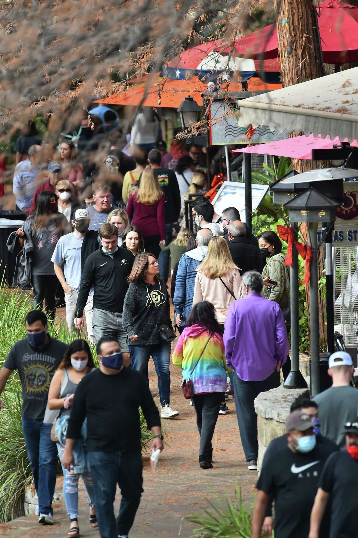People crowd along the Riverwalk Tuesday prior to the Alamo Bowl. Visitors are asked to wear their masks as part of COVID-19 protection protocols.
