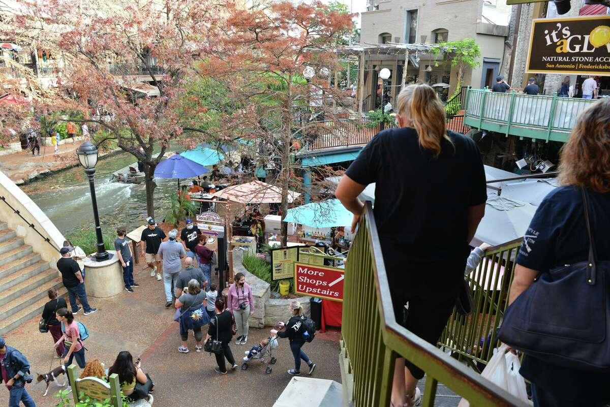 Crowds of people manuever around the Riverwalk Tuesday prior to the Valero Alamo Bowl under COVID-19 protocols.