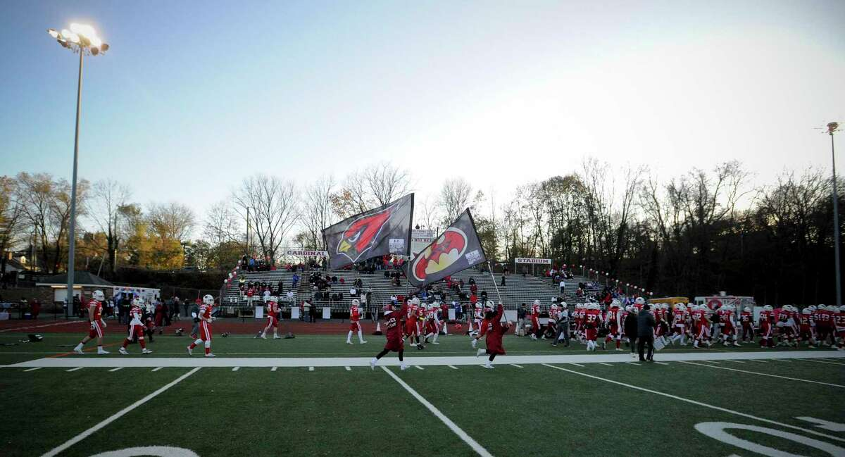 Greenwich takes the field to the cheers of fans at the start of a high school football game against Ridgefield at Cardinal Stadium on Nov. 16, 2019.