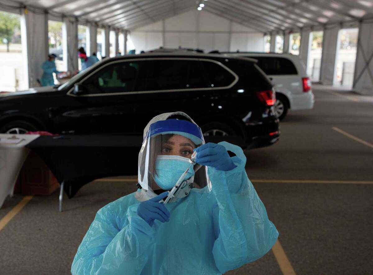 Joyetta Weh prepares a dose of the COVID-19 Moderna vaccine at the drive-through site at Delmar Stadium on Friday, Jan. 29, 2021, in Houston. The site is operated in a partnership between the city and United Memorial Medical Center.