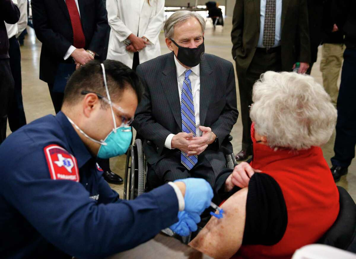 Texas Governor Greg Abbott (center) visits with Barbara Alexander of Bedford as she receives her COVID-19 shot from Arlington firefighter Andrew Harris at a mass vaccination site inside the Esports Stadium Arlington & Expo Center in Arlington, Texas, Monday, January 11, 2021. Alongside local and state officials, Abbott provided an update on COVID-19 vaccine efforts in Texas.