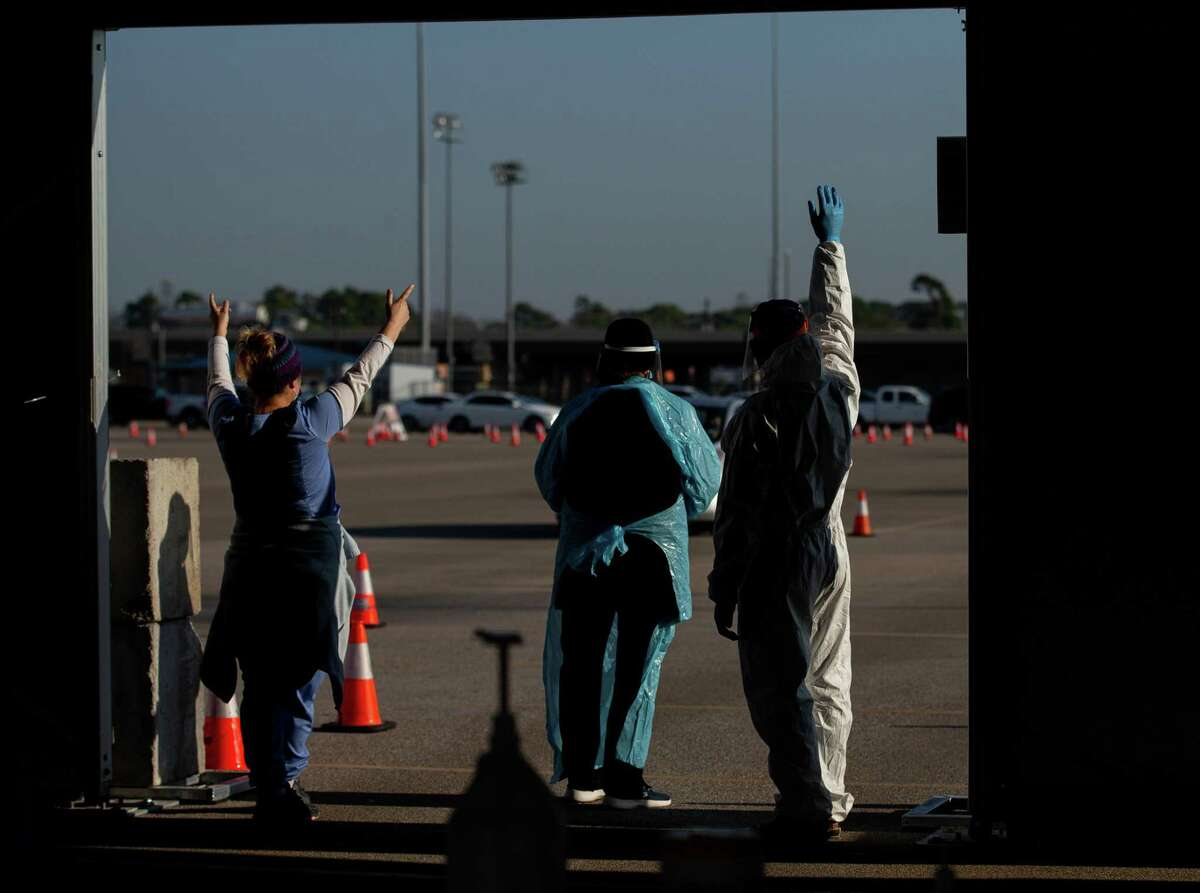 Medical staff welcome motorists at the COVID-19 vaccination drive through at Delmar Stadium on Friday, Jan. 29, 2021, in Houston. The site is operated in a partnership between the city and United Memorial Medical Center.