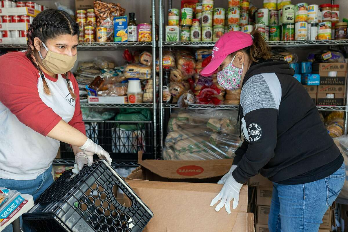 Valeria Fornes (left) and Maria Fornes, volunteers with the Robert Allen Mercy House food pantry, organize donations at the donations container in the parking lot of Shiloh Church in East Oakland.
