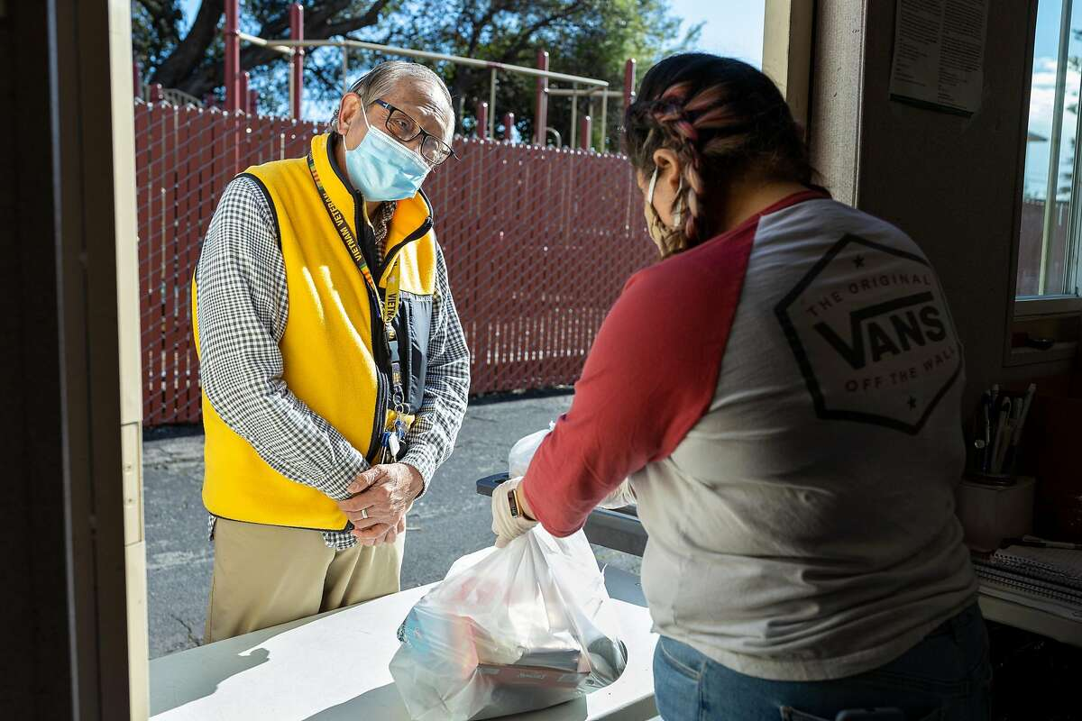 Valeria Fornes (right), a volunteer with the Robert Allen Mercy House food pantry, helps Florencio Diaz at the Robert Allen Mercy House food pantry in the parking lot of Shiloh Church in East Oakland.