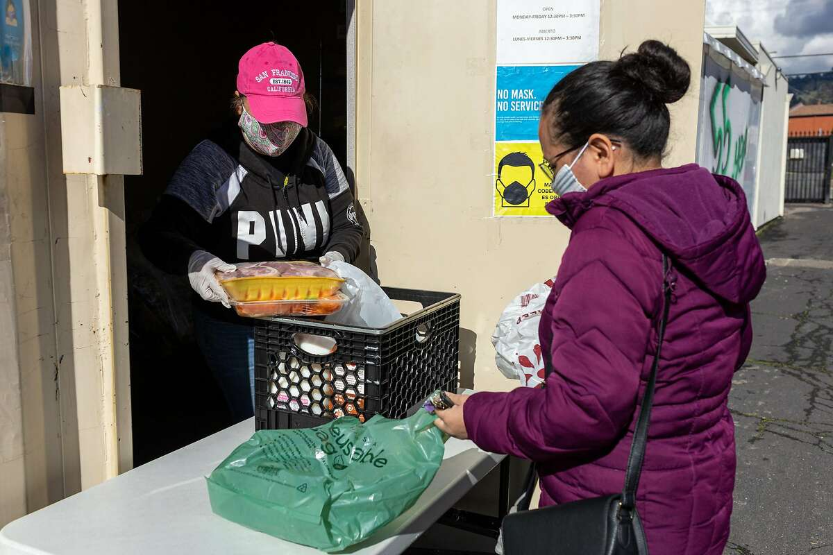 Pantry volunteer Maria Fornes (left) prepares a food bundle for Marta Carballo in East Oakland.