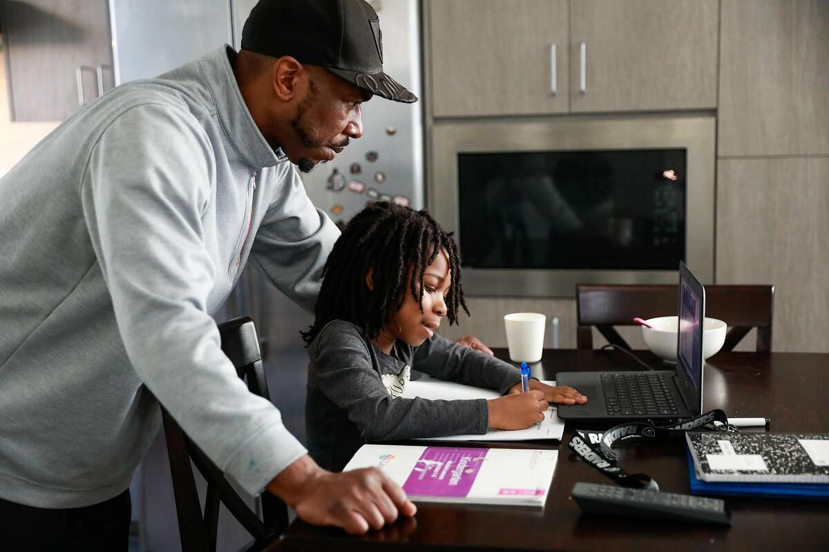 John Jones helps son Josiah, 6, with his virtual learning class at their home in Oakland.