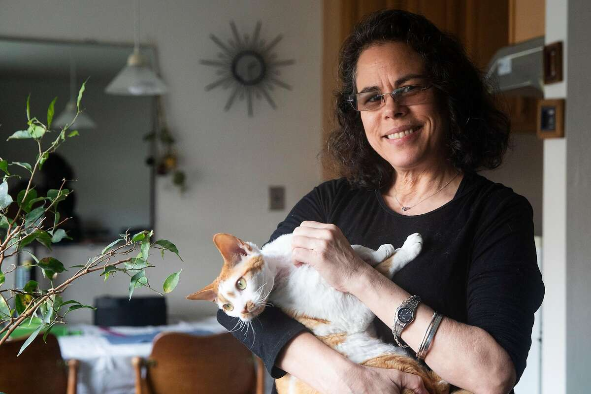 Paola Laverde poses for a portrait with her cat Albert inside of her home in Berkeley, Calif. Thursday, January 28, 2021. Laverde said its critical for communities of color to get culturally appropriate and accurate information on the vaccine.